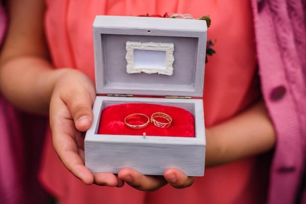 Scatola con fedi nuziali nelle mani della ragazza per la cerimonia di fidanzamento