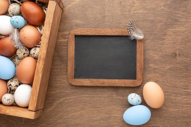 Scatola con le uova per pasqua e lavagna