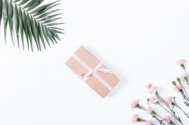 Scatola con un regalo e fiori sulla tavola bianca