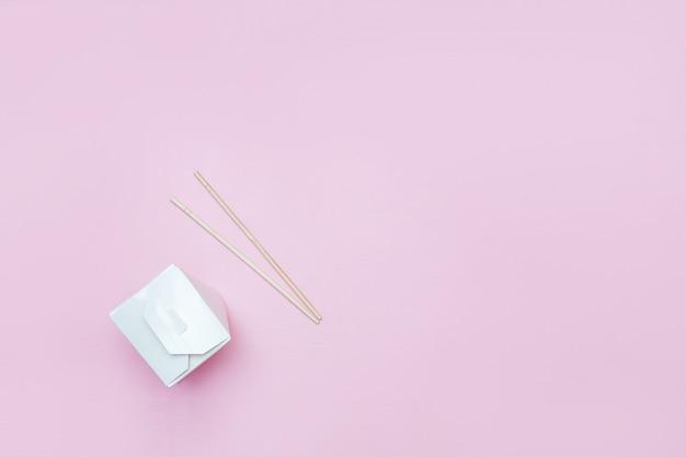 Scatola da asporto aperta per tagliatelle cinesi presentati con le bacchette, su sfondo rosa
