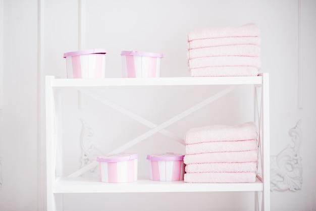 Scatola da donna per accessori e asciugamani puliti rosa sullo scaffale bianco. scaffale con accessori donna in bagno.