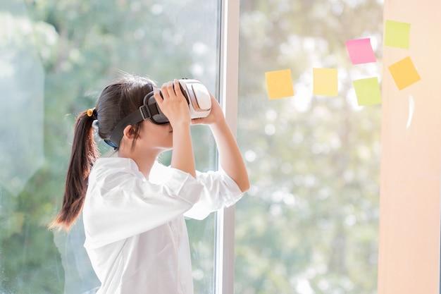 Scatola da portare vr della cuffia avricolare della bella femmina asiatica per il gioco dei media futuri del simulatore del gioco vicino alle finestre