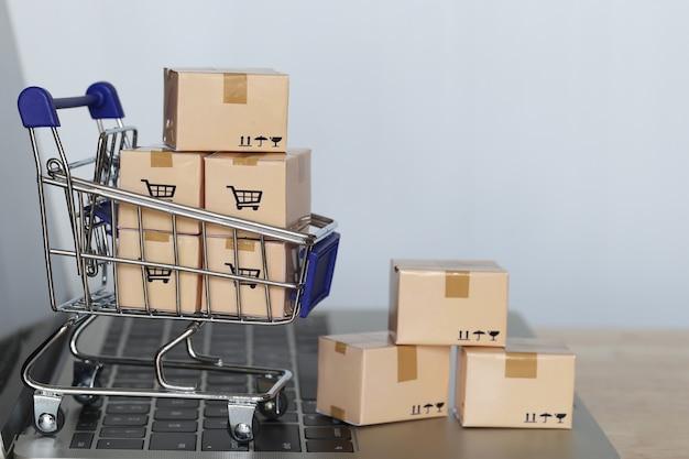 Scatola dei pacchi marrone e carrello in miniatura modello sulla tastiera del computer per lo shopping online
