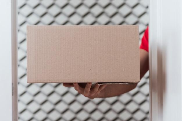 Scatola del primo piano per la consegna e la mano del corriere
