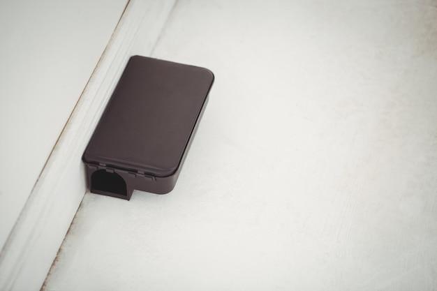 Scatola dell'esca del ratto sul pavimento bianco in una casa