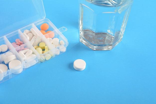 Scatola della medicina con bicchiere d'acqua