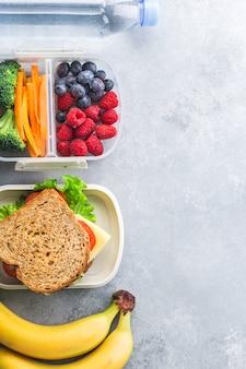 Scatola della refezione con la banana delle bacche delle verdure del panino sulla tavola grigia sana