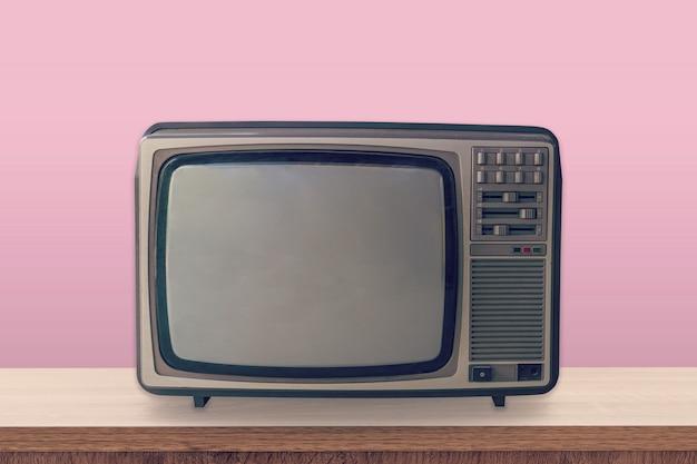 Scatola della tv dell'annata sulla tavola di legno e sul fondo rosa di colore pastello.