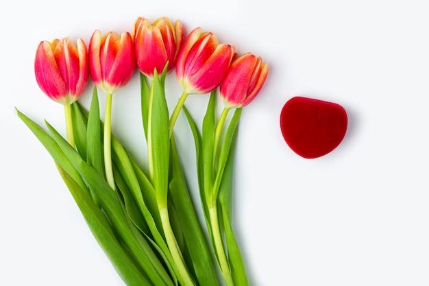 Scatola di anello a forma di cuore rosso chiuso del velluto e un mazzo di cinque tulipani rossi freschi su fondo bianco. regalo per san valentino, festa della donna, compleanno. concetto di proposta di matrimonio