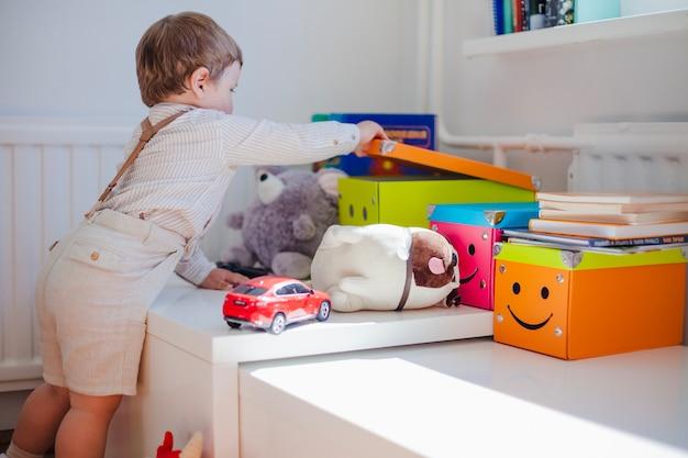 Scatola di apertura del ragazzino con i giocattoli