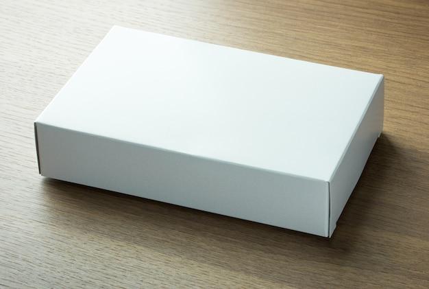 Scatola di carta bianca vuota su sfondo scuro di legno