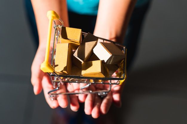 Scatola di carta della tenuta della mano del primo piano in mini carrello usando come commercio elettronico