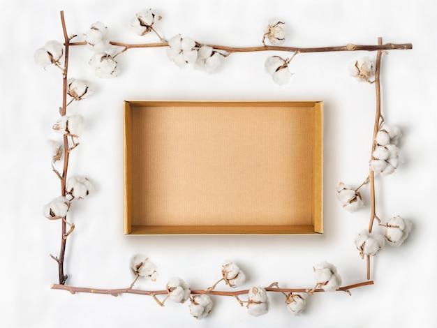 Scatola di cartone all'interno della cornice fatta di rami di fiori di cotone su sfondo bianco. disteso