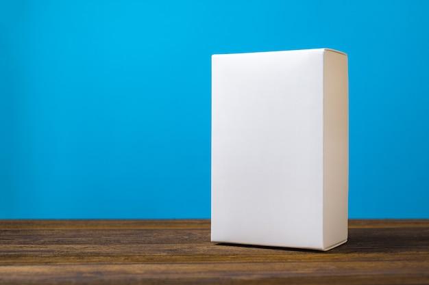 Scatola di cartone bianca del pacchetto vuoto su legno