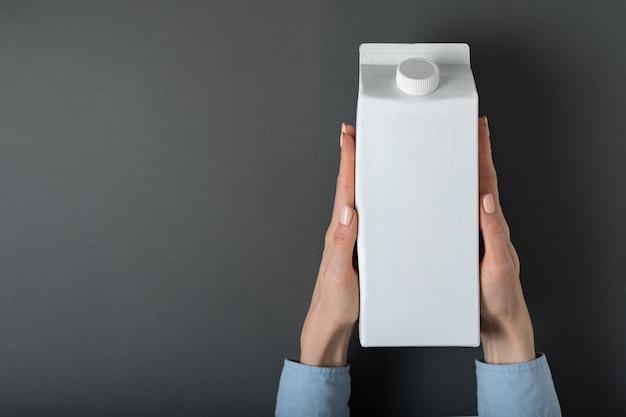 Scatola di cartone bianca o imballaggio del tetra pack con un cappuccio in mani femminili.