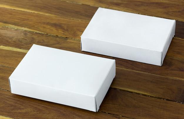 Scatola di cartone bianco vuoto pacchetto sul tavolo di legno scuro