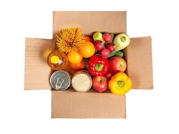 Scatola di cartone con un set di cibo. frutta, verdura, cibo in scatola, olio vegetale, spaghetti. consegna del cibo. set di generi alimentari.
