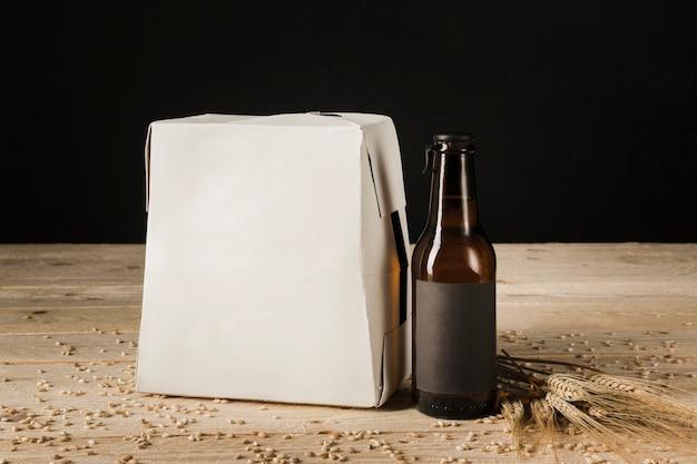 Scatola di cartone della bottiglia di birra su fondo di legno