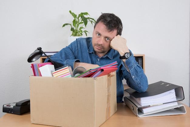 Scatola di cartone di packing files in dell'uomo d'affari all'ufficio