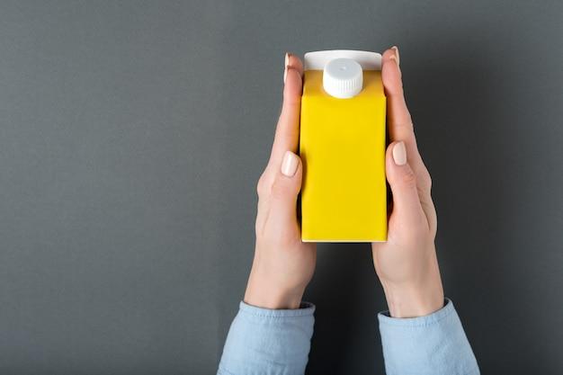 Scatola di cartone gialla o imballaggio del tetra pack con un cappuccio in mani femminili.