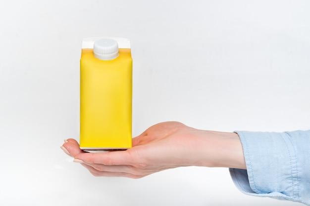 Scatola di cartone gialla o imballaggio del tetra pack con un cappuccio in una mano femminile.