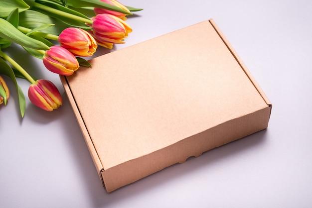 Scatola di cartone marrone e fiori di tulipano su backkground grigio