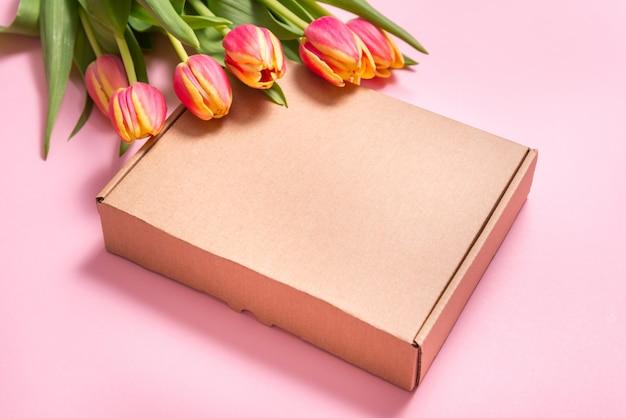 Scatola di cartone marrone e fiori di tulipano su backkground rosa