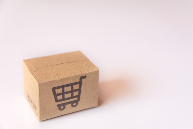Scatola di cartone o pacco con logo carrello supermercato su sfondo bianco. con copia spazio