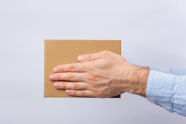 Scatola di cartone quadrata in mani maschili. consegna dei pacchi. vista laterale.