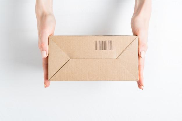 Scatola di cartone rettangolare con codice a barre in mani femminili. vista dall'alto,