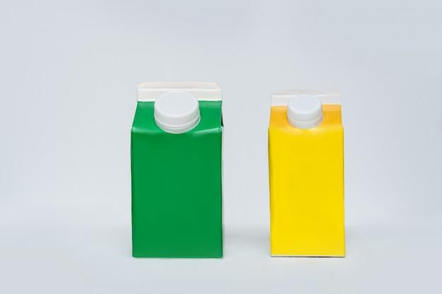 Scatola di cartone verde e gialla o imballaggio del tetra pack con un cappuccio su una superficie bianca.