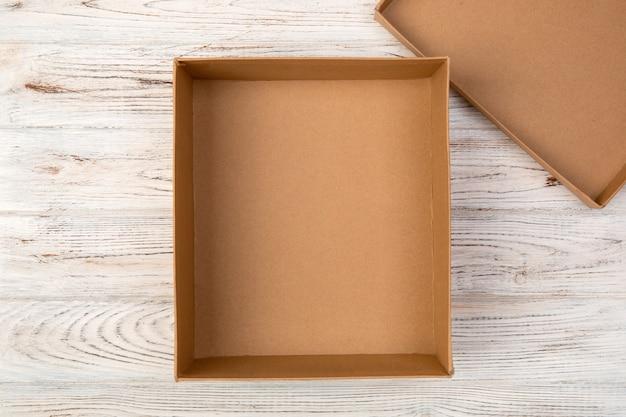 Scatola di cartone vuota aperta su fondo di legno. vista dall'alto