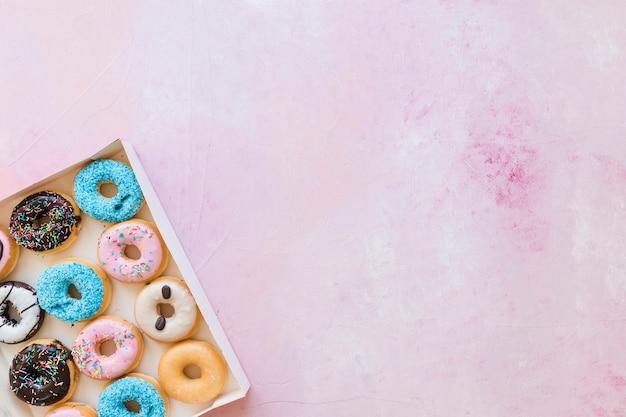 Scatola di ciambelle fresche su sfondo rosa