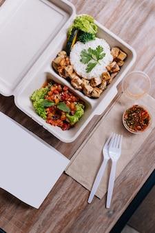 Scatola di cibo pulito: riso con pollo a cubetti servito con insalata di pomodori