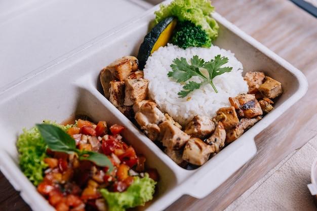 Scatola di cibo pulito: riso con pollo a cubetti servito con insalata di pomodori.