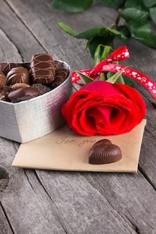 Scatola di cioccolatini, rosa rossa su uno sfondo scuro