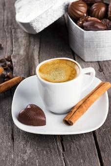 Scatola di cioccolatini, tazza di caffè su un fondo di legno