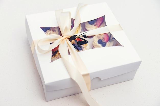 Scatola di consegna con gustosi cupcakes. scatola di carta con cupcakes alla frutta. festa della mamma. festa di compleanno. le vacanze di pasqua celebrano.