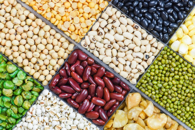 Scatola di diversi cereali integrali fagioli e legumi semi lenticchie e noci sfondo colorato spuntino trama - collage vari fagioli mescolano piselli agricoltura di cibo sano naturale per cucinare ingredienti