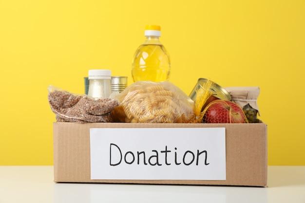 Scatola di donazione con cibo diverso contro lo spazio giallo. volontariato