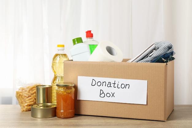 Scatola di donazione con cibo diverso sul tavolo in legno