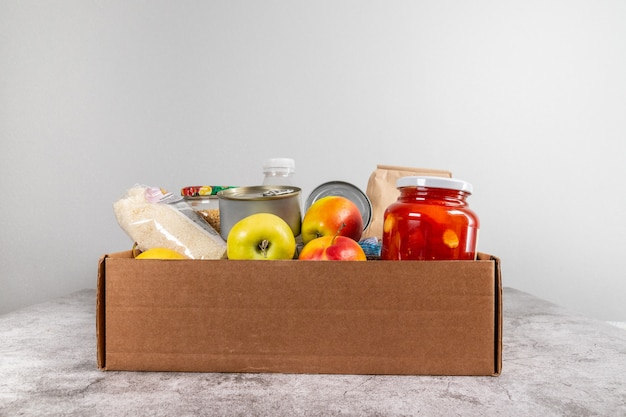 Scatola di donazione con cibo naturale sano, frutta, cereali e conserve su un tavolo grigio