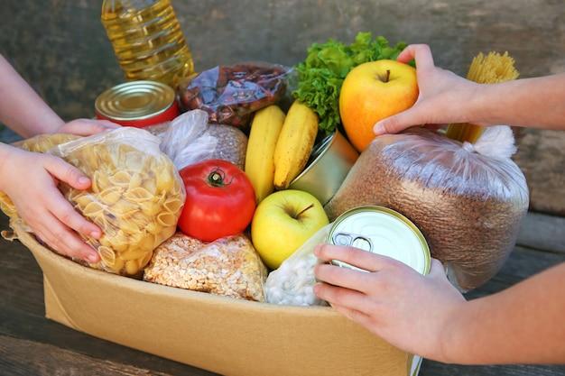 Scatola di donazione con cibo sul vecchio tavolo di legno