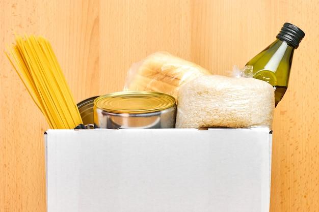 Scatola di donazione con conserve alimentari, pasta e riso su una parete di legno. consegna del cibo o concetto di beneficenza