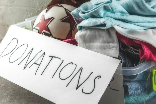 Scatola di donazione con giocattoli, vestiti e cibo