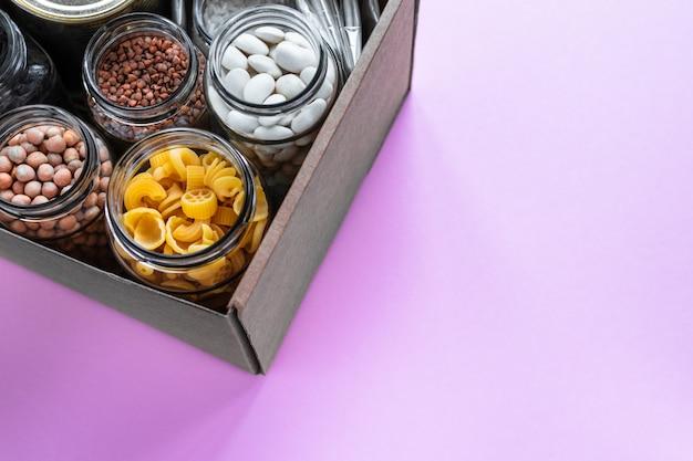 Scatola di donazione con pasta, noci, grano saraceno e fagioli in barattolo di vetro.