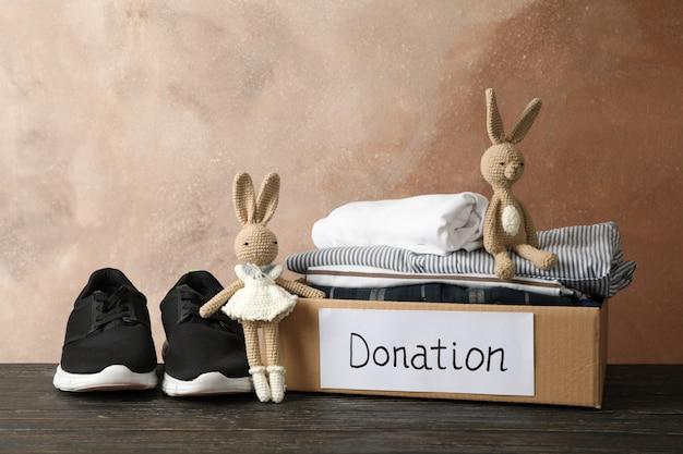 Scatola di donazione con vestiti e giocattoli sul tavolo di legno