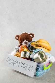 Scatola di donazione in plastica con giocattoli, vestiti e cibo su sfondo grigio bianco