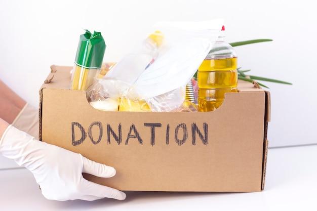 Scatola di donazione. nelle mani in guanti di gomma c'è una scatola di cartone con la donazione scritta con cibo e maschere protettive e un disinfettante su una superficie bianca.