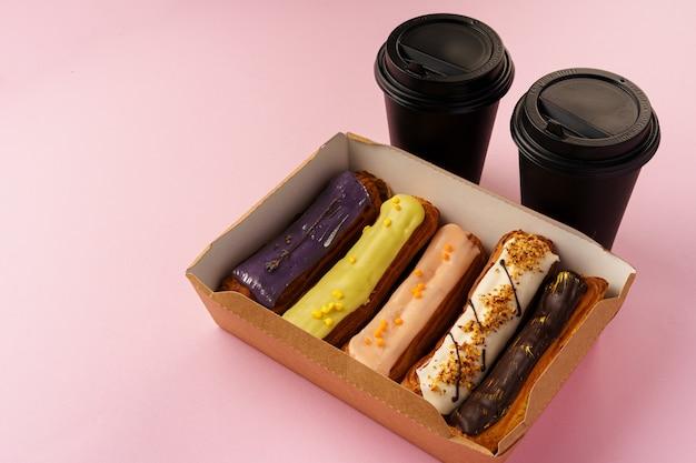 Scatola di eclairs con tazze di caffè da asporto su sfondo rosa